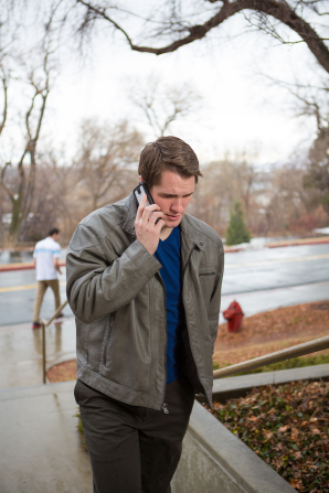 A young man in a gray jacket walks outside while holding a phone close to his ear.