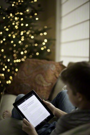 A young man lying on a couch next to a Christmas tree and reading from a tablet.