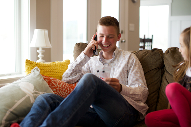 A young man sitting near his sister on a couch while talking and laughing on a phone.