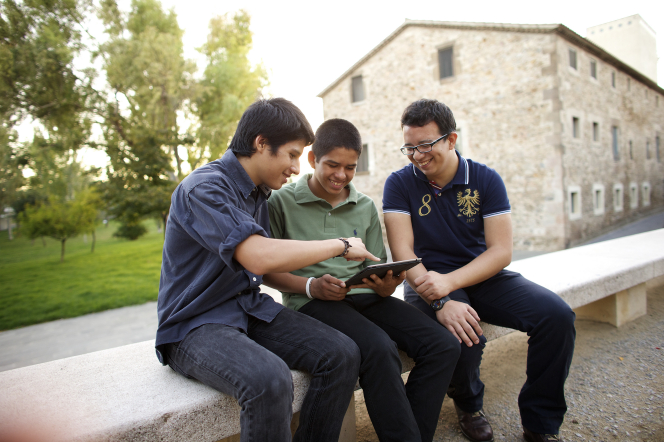 Three young men sit on a bench together and share a tablet.