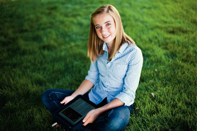 A young woman with blond hair is sitting cross-legged on the grass and holding a tablet.