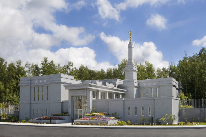 The Anchorage Alaska Temple on a sunny day, with flowers in the front and green trees in the background.