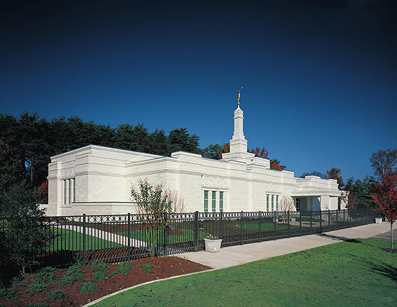 Grass, trees, and a black fence surrounding the Birmingham Alabama Temple.