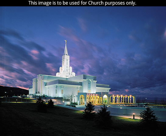 The Bountiful Utah Temple lit up in the evening, with clouds in the sky.