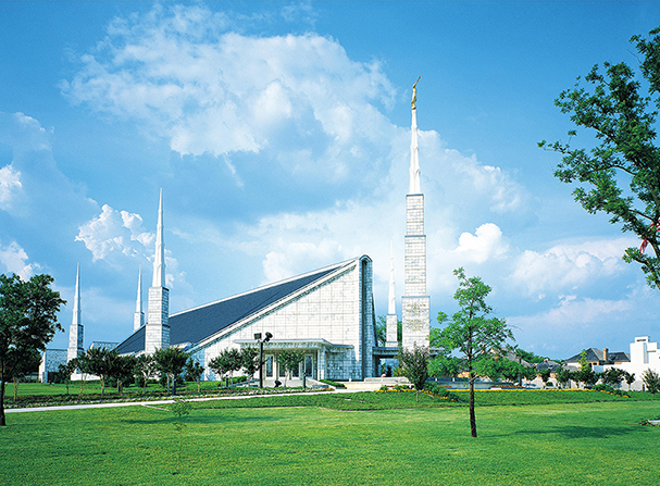 A large lawn in front of the Dallas Texas Temple, with a blue sky and large white clouds overhead.