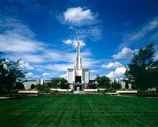A freshly mowed lawn and a fountain in front of the Denver Colorado Temple on a sunny day with a few clouds.