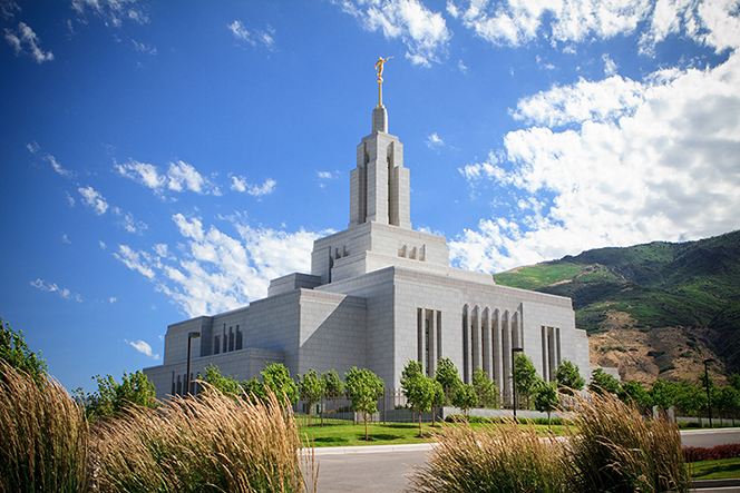 A road and vegetation in front of the Draper Utah Temple, with a mountain in the background and clouds in the sky.