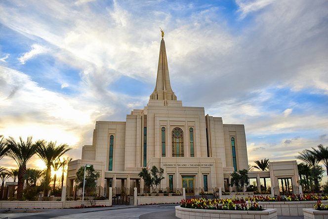 A view of the front entrance to the Gilbert Arizona Temple, with large white clouds overhead and the sun just beginning to set in the background.