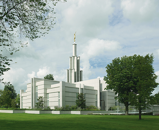 A view of The Hague Netherlands Temple from beyond green lawns, with large white clouds overhead.