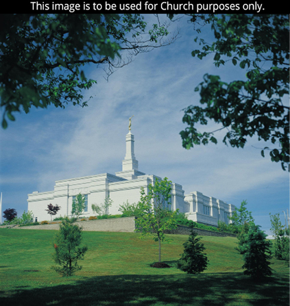 A view from afar of the Halifax Nova Scotia Temple and grounds, with the branches of a tree in the foreground.