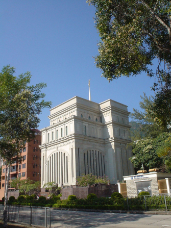 A view of the Hong Kong China Temple from across the street, with large trees growing in the foreground.