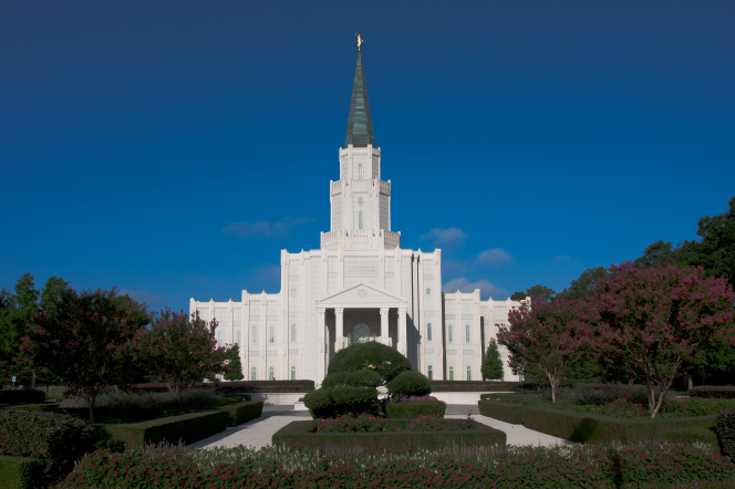 The front of the Houston Texas Temple, with trees and bushes on the grounds.