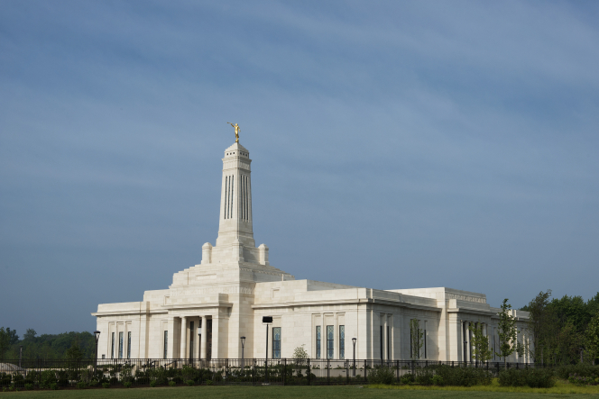 A view of the front and side of the Indianapolis Indiana Temple enclosed by a black fence.