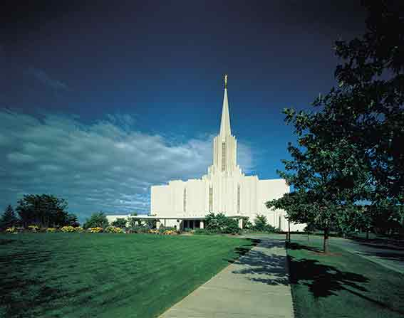 A view of the Jordan River Utah Temple and grounds, with a bright blue sky and one large white cloud overhead.