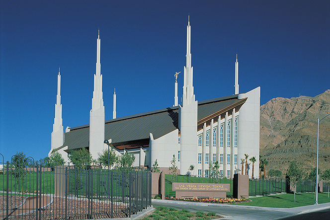 A view of the side of the Las Vegas Nevada Temple, with a large brown mountain in the background and a clear blue sky overhead.