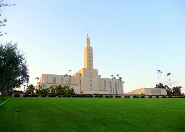A view of the Los Angeles California Temple, with its bright green lawn in the foreground and a clear blue sky overhead.