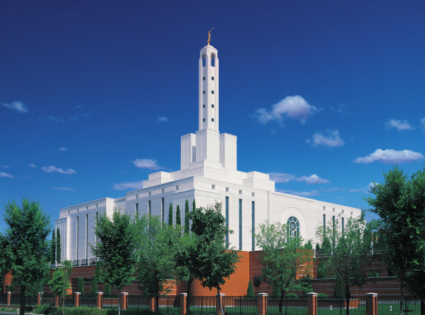 A view from one corner of the Madrid Spain Temple, with green trees growing on the grounds and several small white clouds overhead.