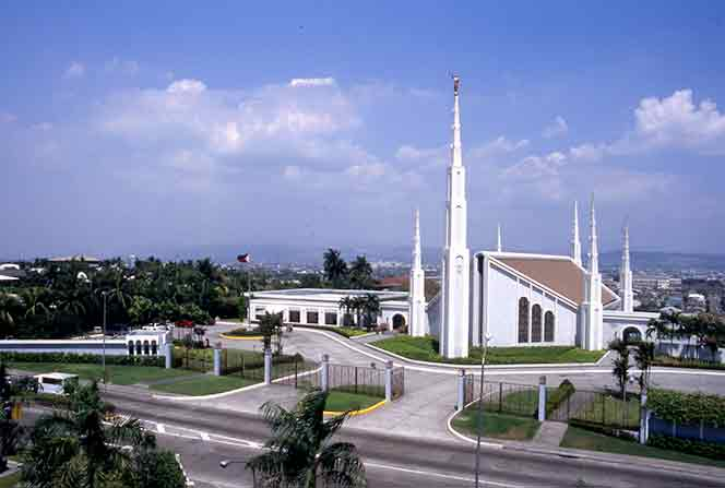 A view of the Manila Philippines Temple and grounds from across the street, with a few white clouds overhead.