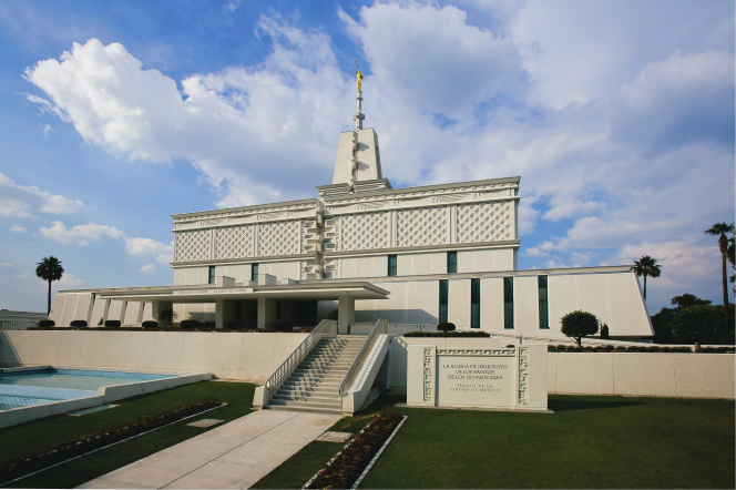 A view of the front and entrance of the Mexico City Mexico Temple, with large white clouds overhead and a green lawn in the foreground.
