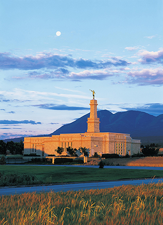 A view from afar of the Monticello Utah Temple in the evening, with the moon barely visible above the clouds.