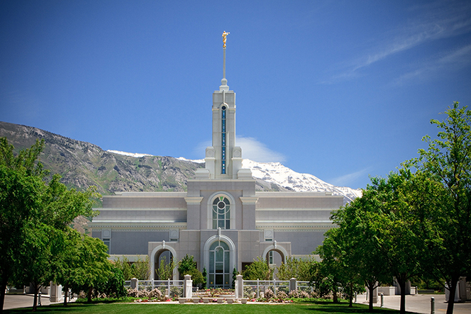 A front view of the Mount Timpanogos Utah Temple, with rows of trees lining the sidewalks and a clear blue sky overhead.