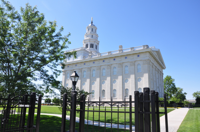 A side view of the Nauvoo Illinois Temple, with a black fence surrounding the grounds and a clear blue sky overhead.