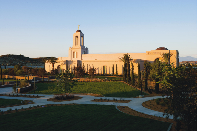A side view of the Newport Beach California Temple in the evening, with a clear, pale blue sky overhead.