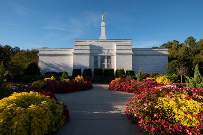 The side of the Raleigh North Carolina Temple at the end of a paved walkway lined with colorful flowers on a sunny day.