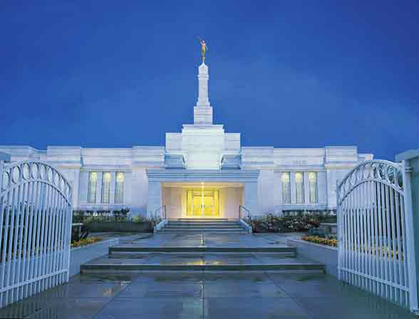 The front of the Oaxaca Mexico Temple in the evening, lit up from within.