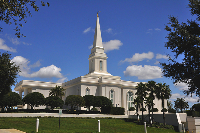 A view of the front of the Orlando Florida Temple, with small trees growing on the grounds and a few white clouds overhead.