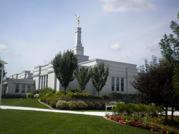 An angled view of the Palmyra New York Temple, with green trees and colorful flowers growing on the grounds.