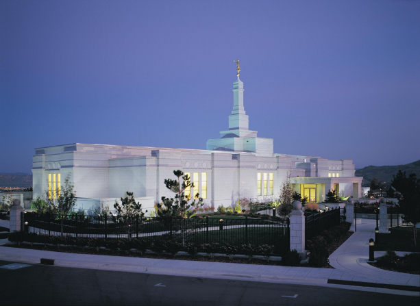 The Reno Nevada Temple in the late evening, with yellow light coming through the windows.