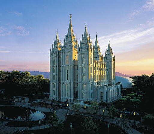 The Salt Lake Temple, with a large pool near the entrance and a pink and orange sunset in the distance.