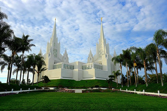A view of the San Diego California Temple from beyond a large green lawn and rows of palm trees.