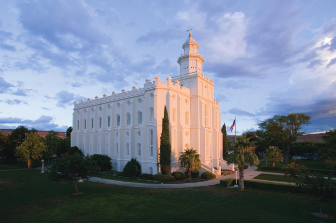 A view of the St. George Utah Temple in the early evening, with the green lawn in the foreground and a U.S. flag near the entrance.