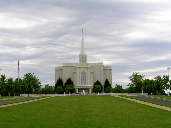 The St. Louis Missouri Temple, with a green lawn in the foreground and light gray clouds overhead.