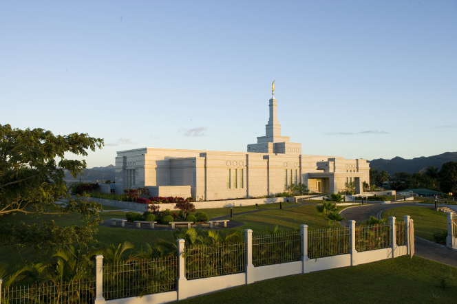 The Suva Fiji Temple in the late afternoon, with the grounds and fence in the foreground.