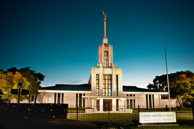 A view from the front of the Sydney Australia Temple in the low light of the evening, including the name sign on the black gate.