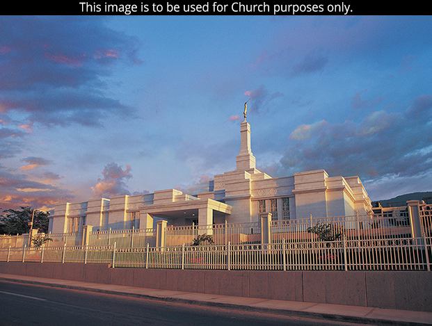 The Tuxtla Gutiérrez Mexico Temple behind two white fences, with a partly cloudy sky overhead.