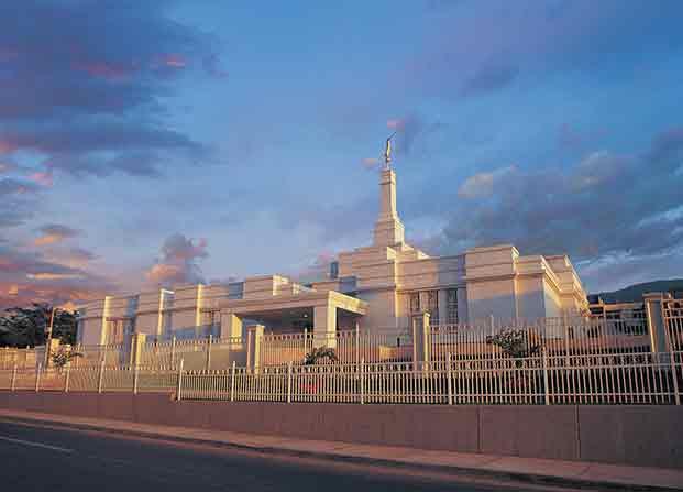 The Tuxtla Gutiérrez Mexico Temple behind two white fences, with a partly cloudy sky overhead.