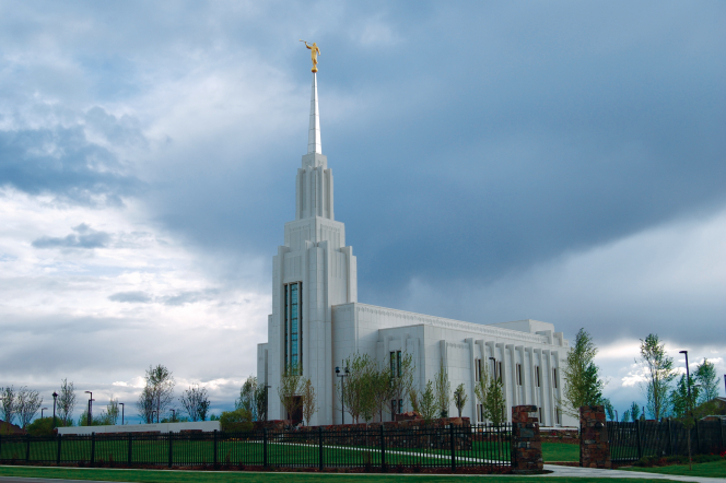 The front and side of the Twin Falls Idaho Temple behind a black fence on a cloudy day.