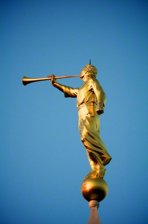 A view of the angel Moroni from the side, with a clear, deep blue sky in the background.