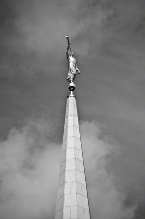 A black-and-white image showing the statue of the angel Moroni on top of the Preston England Temple with clouds in the background.