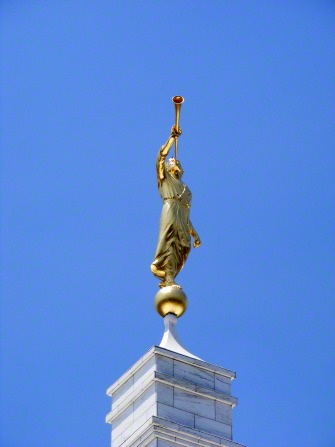The angel Moroni statue seen atop the Raleigh North Carolina Temple on a clear day with a bright blue sky in the background.