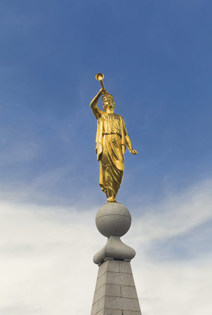 A view of the front of the angel Moroni statue standing on top of the spire of the Salt Lake Temple, with thin white clouds seen in the background.