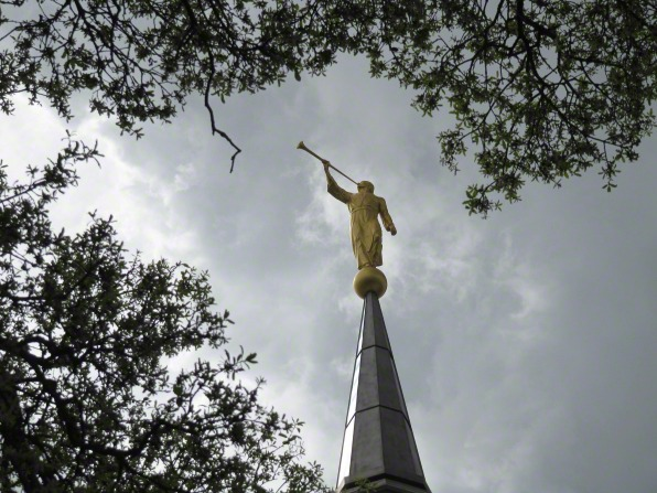 An image of the golden angel Moroni statue atop the spire of the Sacramento California Temple, with the leaves of trees seen nearby.