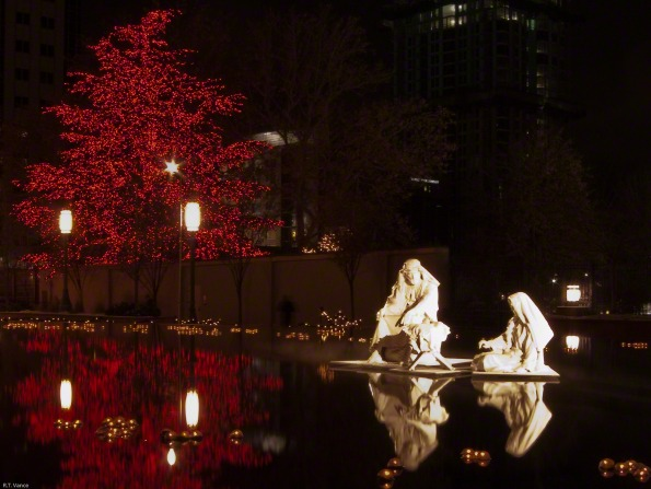 Statues of Joseph and Mary in the reflecting pool at the Main Street Plaza in Salt Lake City, with red Christmas lights on trees in the background.