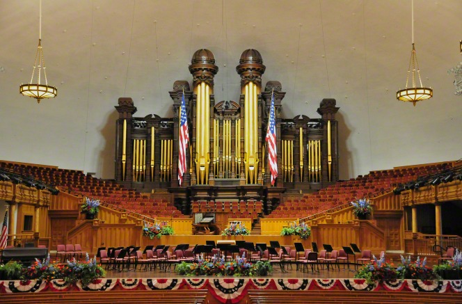 The interior of the Salt Lake Tabernacle, looking toward the organ pipes, with two large U.S. flags hanging from them and a row of flag banners hanging from the stage.