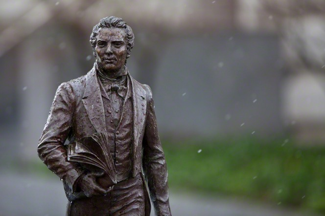 A small bronze statue of Joseph Smith seen outside on Temple Square on a snowy day.