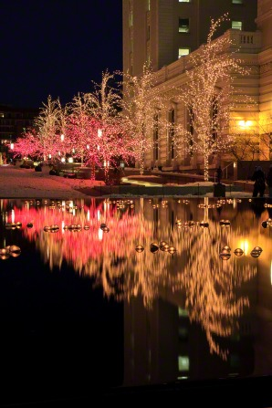 Christmas tree lights in yellow and red reflected in a pool of water near a building on Temple Square, with snow on the ground.